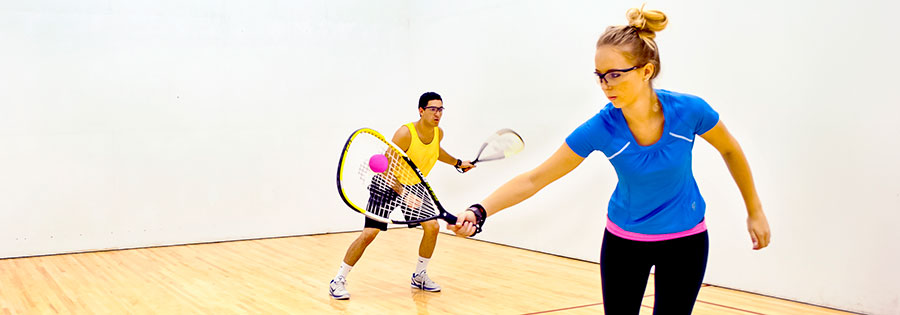 A man and a woman playing racquetball on an indoor court